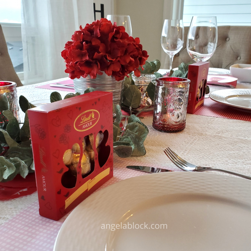 Valentine's Day flowers and candles and cute chocolates as table décor